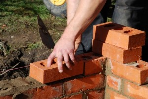Construction worker laying red bricks